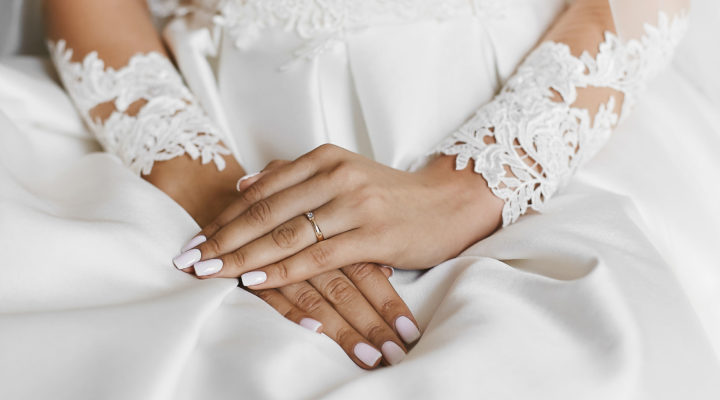 Beautiful female hands with the wedding ring and elegant manicure, a symbol of love.