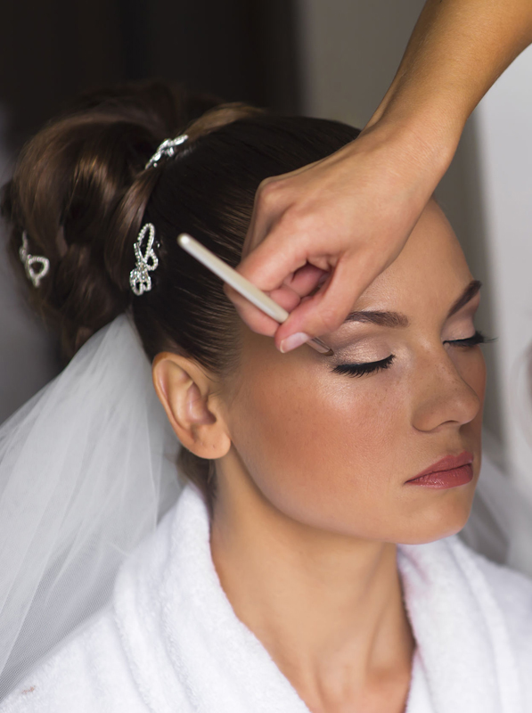 The visagist is correcting makeup. The bride closed her eyes.